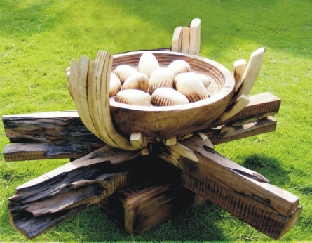Wood Sculpture titled 'Hunger Creates Destroys' by artist Indira Ghosh